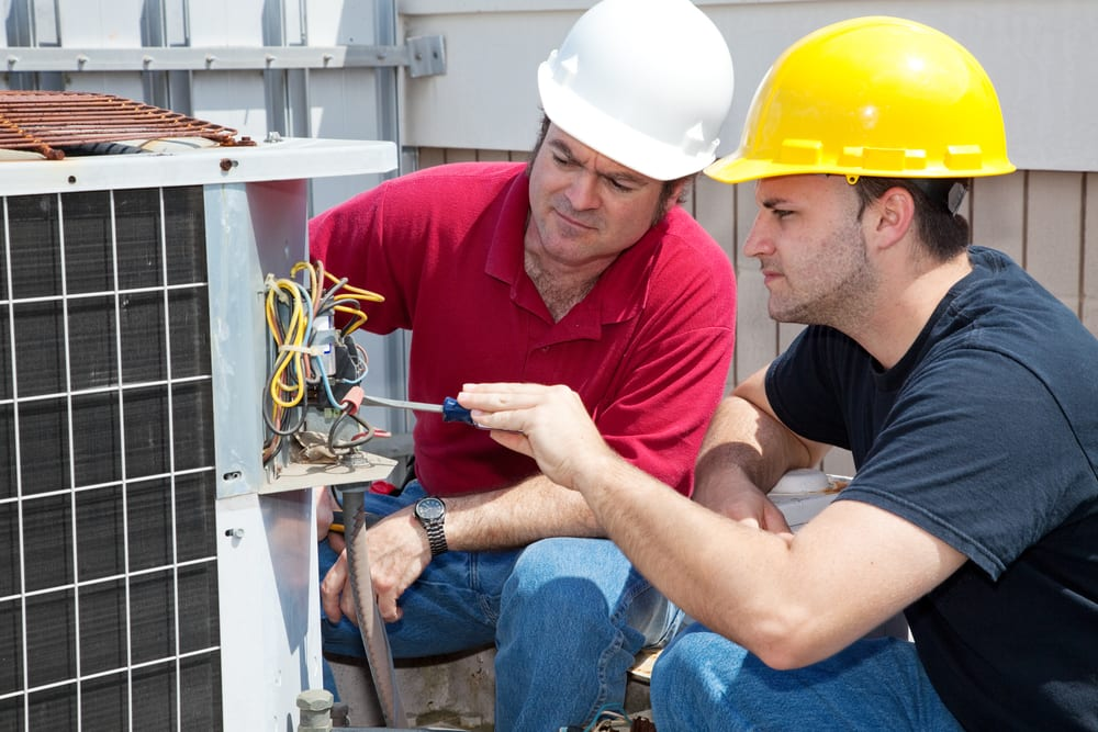 Two service man working on an industrial AC units electrical wiring