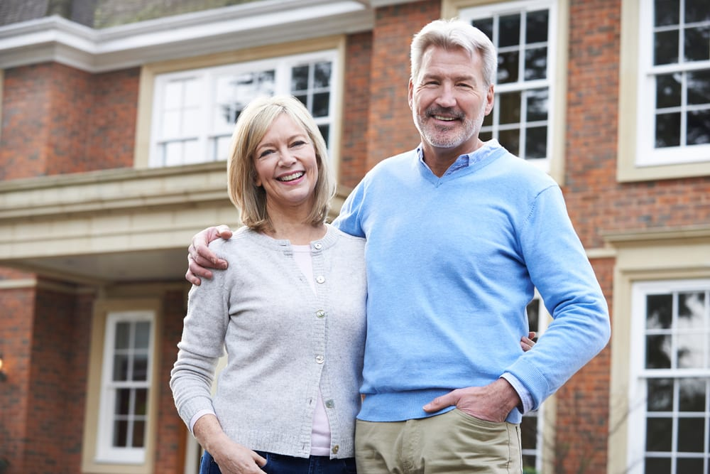 A happy middle aged couple in front of a nice home