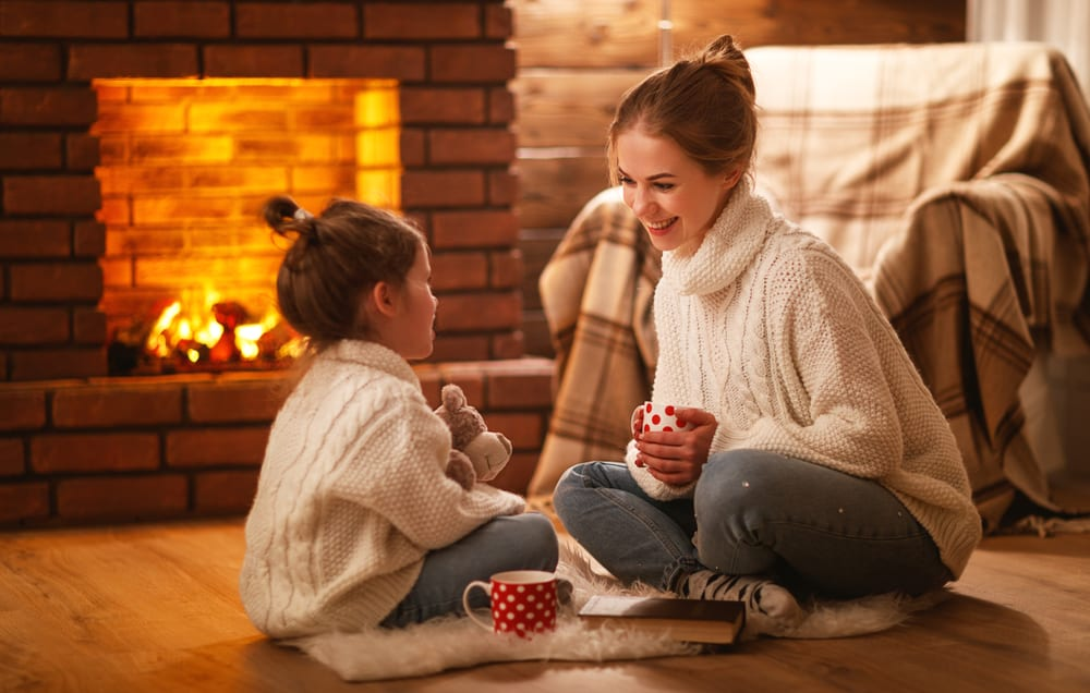 mother and daughter in front of a cozy fireplace